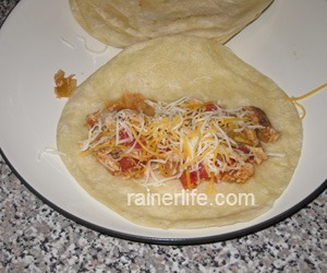 Tortilla with chicken mixture topped with cheese.