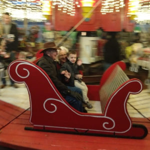 Gavin with his Honey and Pappaw on a carousel | rainerlife.com
